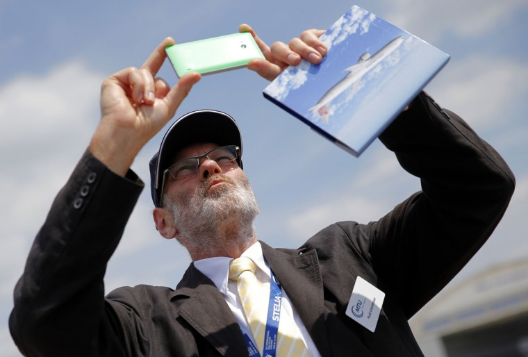 A man takes a picture of an Airbus A380 during a demonstration flight of the Paris Air Show, at Le Bourget airport, north of Paris, Wednesday, June 17, 2015. Some 300,000 aviation professionals and spectators are expected at this weekís Paris Air Show, coming from around the world to make business deals and see dramatic displays of aeronautic prowess and the latest air and space technology. (AP Photo/Christophe Ena)