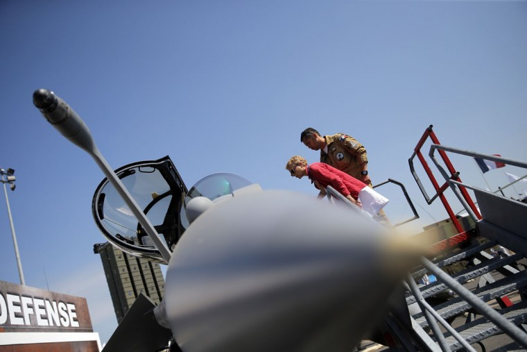 A pilots shows to visitor a Rafale jet fighter during the Paris Air Show, at Le Bourget airport, north of Paris, Wednesday, June 17, 2015. Some 300,000 aviation professionals and spectators are expected at this weekís Paris Air Show, coming from around the world to make business deals and see dramatic displays of aeronautic prowess and the latest air and space technology. (AP Photo/Christophe Ena)