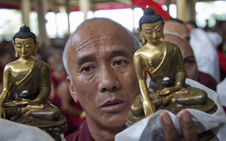 An exile Tibetan Buddhist monk carrying a Buddha statue waits for his turn to offer traditional gifts to his spiritual leader the Dalai Lama during an official prayer ceremony to celebrate his 80th birthday in Dharmsala, India, Sunday, June 21, 2015. The Dalai Lama was born on July 6 according to the Gregorian calendar but his birthday this year falls on June 21 according to the lunar calendar followed traditionally by Tibetans. (AP Photo/Ashwini Bhatia)