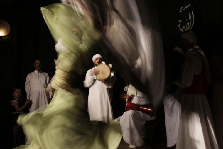 In this Thursday, April 30, 2015 photo, a whirling dervish spins during a performance in collaboration with the Al-Tannoura Egyptian Heritage Dance Troupe at the El Dammah Theatre in Cairo, Egypt. The art form draws its roots from the ecstatic movements of Sufi Muslim mystics seeking a state of delirious oneness with God. (AP Photo/Amr Nabil)