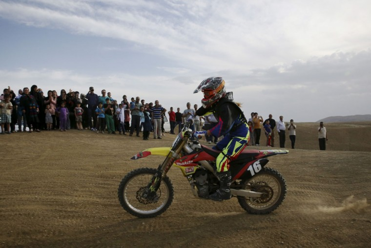 In this photo taken Friday, June 5, 2015, Behnaz Shafiei rides her motocross bike during her training session while fans watch riders at a racetrack near the village of Baraghan, some 19 miles (30 kilometers) west of the capital Tehran, Iran. On a recent weekend, she drew a crowd when she took off her helmet, part of a lot of gear from her international sponsors. Women crowded around Shafiei to take snapshots with her. (AP Photo/Vahid Salemi)