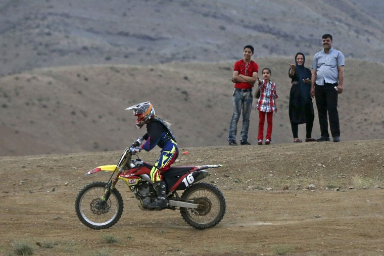 "In this photo taken Friday, June 5, 2015, fans watch Iranian Behnaz Shafiei ride her motocross bike during a training session at a racetrack in the Alborz mountain range near the village of Baraghan, some 19 miles (30 kilometers) west of the capital Tehran, Iran. ""My goal is to be a pioneer to inspire other women,î she said. ìTogether, we can convince authorities to recognize womenís motorcycle racing."" (AP Photo/Vahid Salemi)"