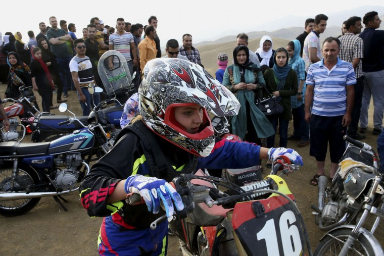 "In this photo taken Friday, June 5, 2015, Iranian Behnaz Shafiei pushes her motocross bike by a racetrack as she takes a break during her riding session on the outskirts of Baraghan, some 19 miles (30 kilometers) west of the capital Tehran, Iran. ""My goal is to be a pioneer to inspire other women,î she said. ìTogether, we can convince authorities to recognize womenís motorcycle racing."" (AP Photo/Vahid Salemi)"