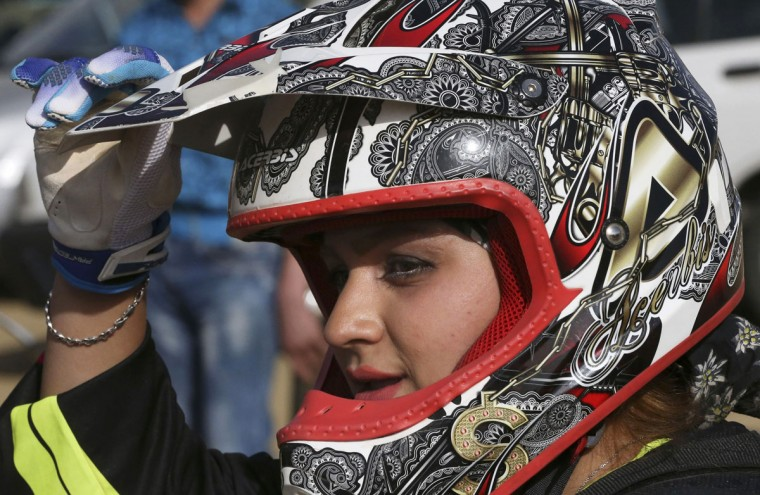 "In this photo taken Friday, June 5, 2015, Iranian motocross rider Behnaz Shafiei takes a break during a training session at a racetrack near the village of Baraghan, some 19 miles (30 kilometers) west of the capital Tehran, Iran. ""When two days pass and I do not ride my motorcycle, I get really ill. Even the thought of not having a motorcycle some day gives me an awful feeling,"" Shafiei said. (AP Photo/Vahid Salemi)"