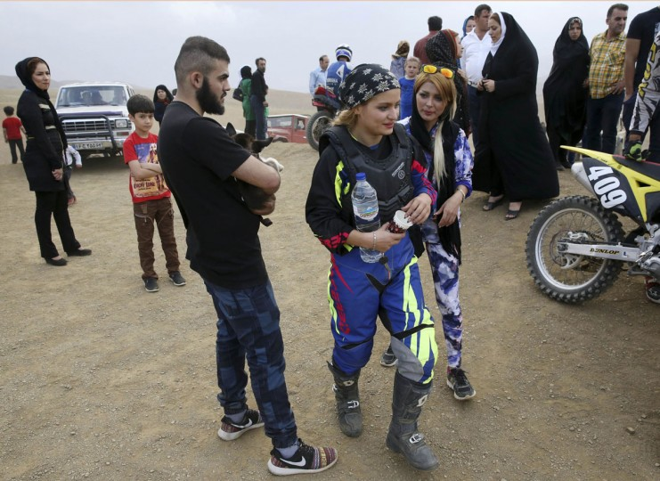 "In this photo taken Friday, June 5, 2015, Elma Ajdari, center right with sunglasses, talks to motocross rider Behnaz Shafiei during Shafiei's training session at a racetrack near the village of Baraghan, some 19 miles (30 kilometers) west of the capital Tehran, Iran. ""My goal is to be a pioneer to inspire other women,î she said. ìTogether, we can convince authorities to recognize women's motorcycle racing."" (AP Photo/Vahid Salemi)"