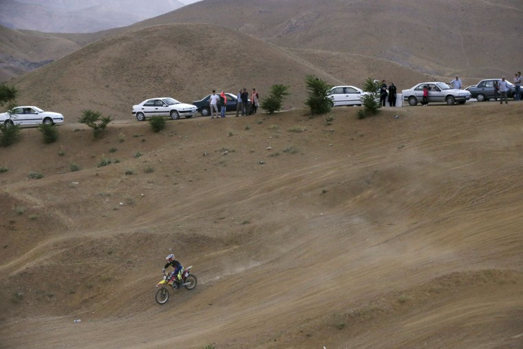 In this photo taken Friday, June 5, 2015, fans watch Iranian motocross rider Behnaz Shafiei descend on a hill during a training session near the village of Baraghan some 19 miles (30 kilometers) west of the capital Tehran, Iran. (AP Photo/Vahid Salemi)