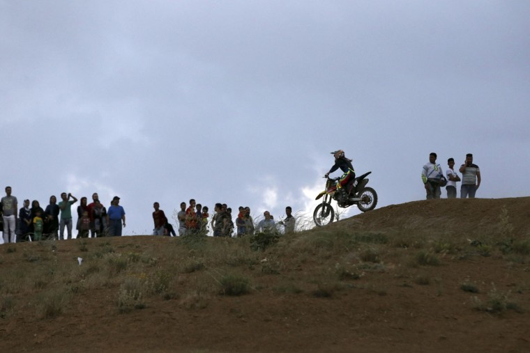 In this photo taken Friday, June 5, 2015, Iranian Behnaz Shafiei rides her motocross bike during her training session while fans watch riders at a racetrack near the village of Baraghan, some 19 miles (30 kilometers) west of the capital Tehran, Iran. (AP Photo/Vahid Salemi)