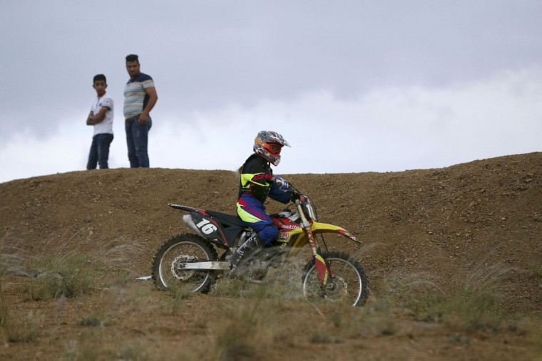 In this photo taken Friday, June 5, 2015, fans watch Iranian Behnaz Shafiei ride her motocross bike during a training session at a racetrack in the Alborz mountain range near the village of Baraghan, some 19 miles (30 kilometers) west of the capital Tehran, Iran. (AP Photo/Vahid Salemi)