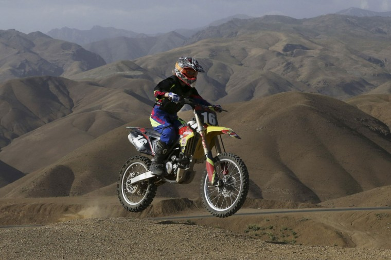 In this photo taken Friday, June 5, 2015, Behnaz Shafiei rides her motocross bike during her training session at a racetrack in the Alborz mountain range near the village of Baraghan, some 19 miles (30 kilometers) west of the capital Tehran, Iran. Shafiei fell in love with motorcycles 11 years ago when she saw a countrywoman running errands on a small bike. (AP Photo/Vahid Salemi)