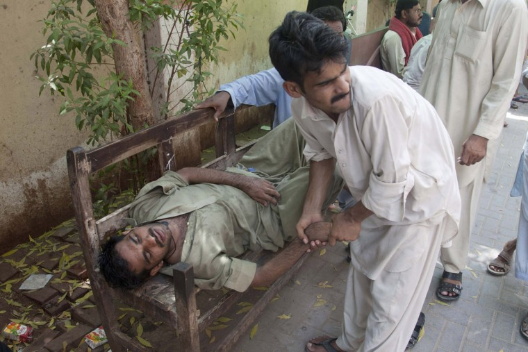A man tries to help another who has fainted due to the heat at a roadside in Karachi, Pakistan, Tuesday, June 23, 2015. A scorching heat wave across southern Pakistan's city of Karachi has killed more than 400 people, authorities said Tuesday, as morgues overflowed with the dead and overwhelmed hospitals struggled to aid those clinging to life. (AP Photo/Shakil Adil)