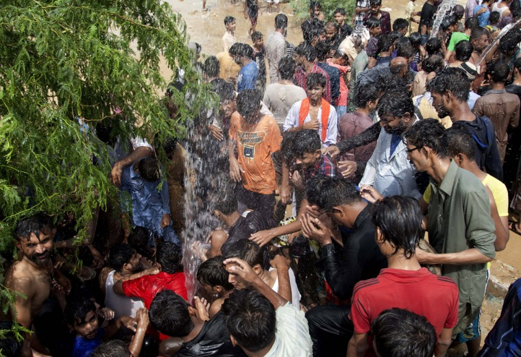 People cool themselves off with water in Karachi, Pakistan, Tuesday, June 23, 2015. A scorching heat wave across southern Pakistan's city of Karachi has killed more than 400 people, authorities said Tuesday, as morgues overflowed with the dead and overwhelmed hospitals struggled to aid those clinging to life. (AP Photo/Shakil Adil)