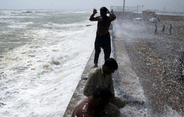 People cool themselves off at Karachi's shore in Pakistan, Tuesday, June 23, 2015. A scorching heat wave across southern Pakistan's city of Karachi has killed more than 400 people, authorities said Tuesday, as morgues overflowed with the dead and overwhelmed hospitals struggled to aid those clinging to life. (AP Photo/Shakil Adil)