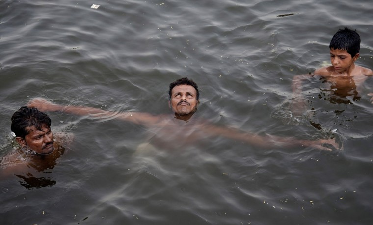 People cool themselves off in polluted water near a port during a high heat wave, in Karachi, Pakistan, Monday, June 22, 2015. More than 100 people have died from heatstroke in the southern Pakistani port city of Karachi in the last two days, officials said Monday. (AP Photo/Shakil Adil)