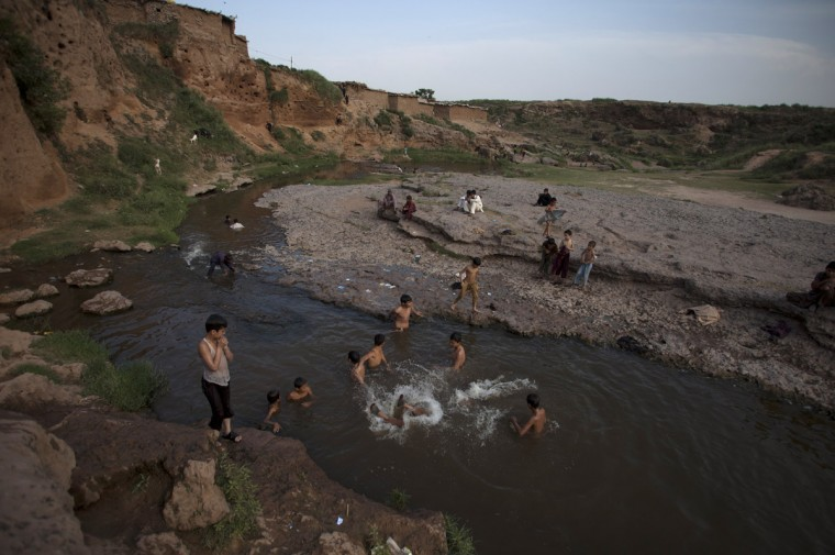 Pakistani children cool off in a polluted canal in Islamabad, Pakistan, where temperature rose on Friday, May 29, 2015. Many cities in Pakistan are facing heat wave conditions with temperatures reaching 46 degrees Celsius (114.8 Fahrenheit) in some places. (AP Photo/B.K. Bangash)