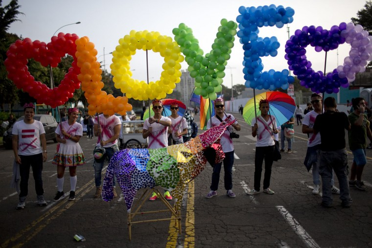 "Revelers hold balloons, representing the colors of a rainbow, to form the word, ""Love"" during the annual gay pride parade in Lima, Peru, Saturday, June 27, 2015. (AP Photo/Rodrigo Abd)"