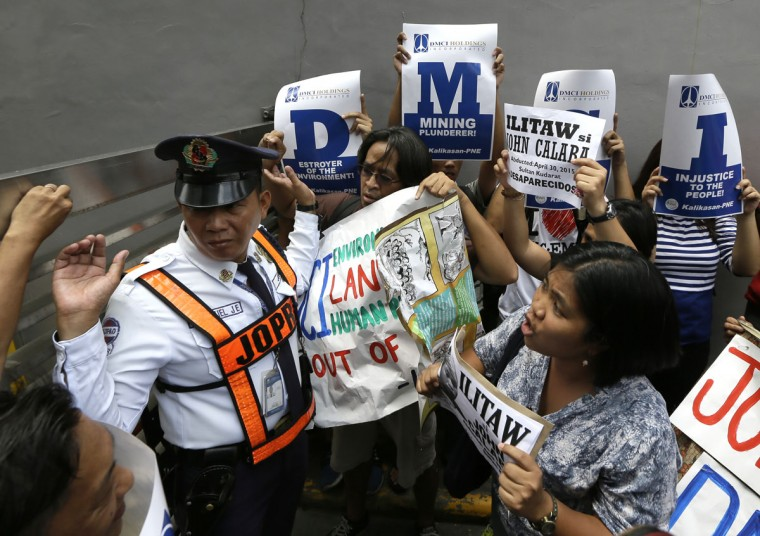 A private guard tries to prevent protesters from surging towards the gates of DMCI, a construction and mining company, to deliver a petition letter during a rally to coincide with World Environment Day, Friday, June 5, 2015 at the financial district of Makati city, east of Manila, Philippines. The protesters, in their statement, scored the company over the disappearance of tribal leader John Calaba and issues of environmental destruction such as mining inside the indigenous people's areas in southern Philippines and building a coal-powered plant that allegedly pollute the environment. (AP Photo/Bullit Marquez)