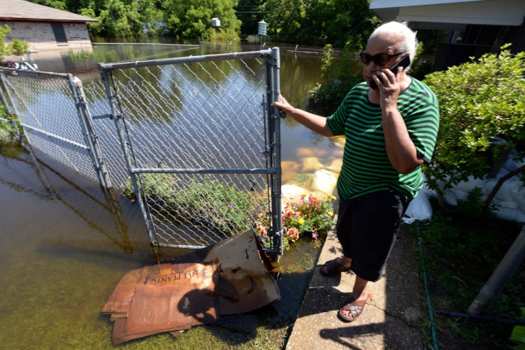 Ophelia Phelps talks to her daughter on the phone after flood water made it's way into her home on Wednesday, June 10, 2015 in Shreveport, La. The Red River leveled off at Shreveport on Tuesday. It reached 37.09 feet in the afternoon, meteorologist Davyon Hill said. (Douglas Collier /The Shreveport Times via AP)