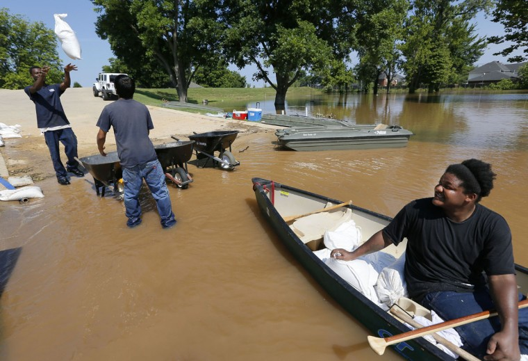 Cedrick Walker, left, throws a sandbag to Josh Firmin, center, as Troy Boyd waits to take it to a house they are trying to protect from water caused by the flooding of the Red River, Thursday, June 11, 2015, in Shreveport, La. Flooding from the swelling river put hundreds of homes and farmland underwater or in danger in rural northwest Louisiana, and state officials said Thursday that they would seek a federal disaster declaration to get help for residents. (AP Photo/Jonathan Bachman)