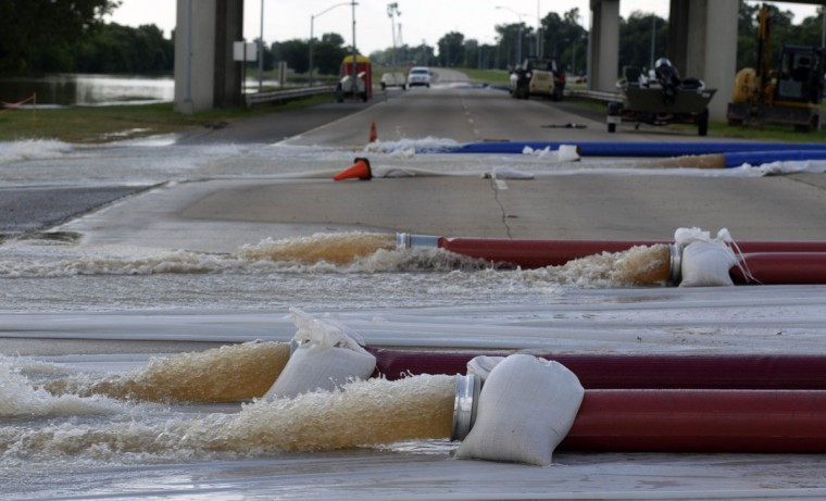 Water is pumped from the Red River away from sewer lines in Bossier City, La. on Tuesday, June 9, 2015 along the Arthur Ray Teague Parkway. The Red River crested Monday and likely will stay at or around its current level for the next few days before slowly decreasing, National Weather Service meteorologist Davyon Hill said. At one point this week, the river was at 37.02 feet, the highest since April 1945, he said. (Douglas Collier/The Shreveport Times via AP)