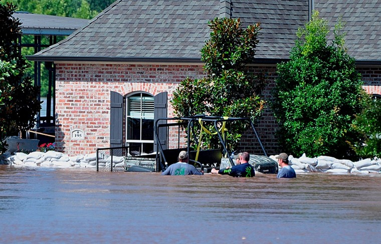 In this Tuesday, June 9, 2015 photo provided by the Bossier Parish Sheriff's Office, residents of the Red Bluff subdivision move through high water, in Bossier City, La. The Red River crested Monday and likely will stay at or around its current level for the next few days before slowly decreasing, National Weather Service meteorologist Davyon Hill said. At one point this week, the river was at 37.02 feet, the highest since April 1945, he said. (Lt. Bill Davis/Bossier Parish Sheriff's Office via AP)