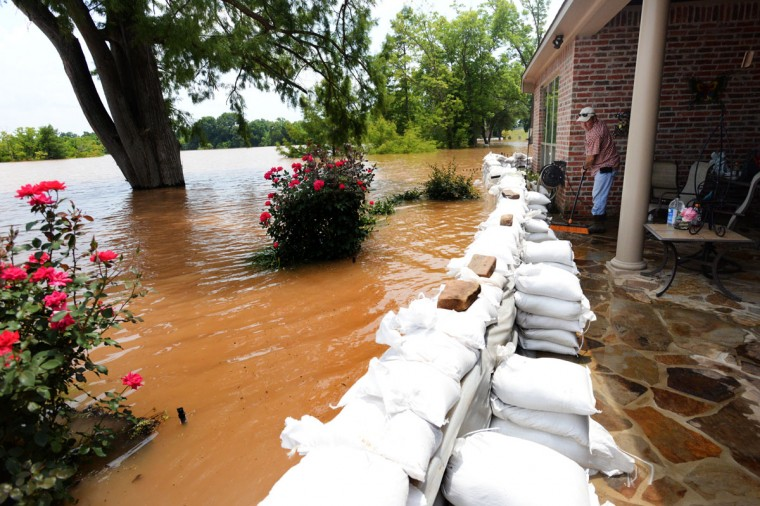 Kevin Parker sweeps water off the patio of his friends house Monday, June 8, 2015, in the Les Maisons Sur La Rouge subdivision in Shreveport, La., where the only thing stopping water from coming into house is the sand bag wall. (Henrietta Wildsmith/The Shreveport Times via AP)