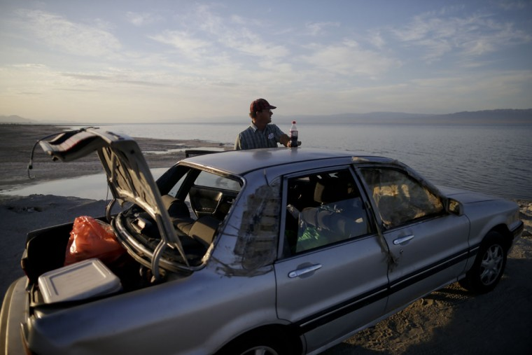 """In this May 1, 2015, photo, Mark Messenger looks out over the Salton Sea as he prepares to sleep in his car on the banks in Salton City, Calif. Often called the """"The Accidental Sea,"""" because it was created when the Colorado River breached a dike in 1905, Salton Sea now faces a looming calamity as coastal Southern California clamors for more water. (AP Photo/Gregory Bull)"""