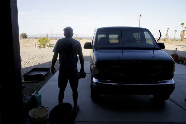 """In this May 1, 2015 picture, Frank Price, 65, stands under in the shade of his garage as he cleans his car in Salton Sea Beach, Calif. Often called the """"The Accidental Sea,"""" because it was created when the Colorado River breached a dike in 1905, Salton Sea now faces a looming calamity as coastal Southern California clamors for more water. (AP Photo/Gregory Bull)"""