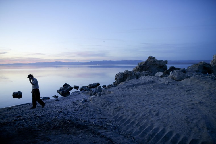 """In this April 29, 2015, photo, biologist Tom Anderson of the Sonny Bono Salton Sea National Refuge Complex makes a call along the receding banks of the Salton Sea near Niland, Calif. Often called the """"The Accidental Sea,"""" because it was created when the Colorado River breached a dike in 1905, Salton Sea now faces a looming calamity as coastal Southern California clamors for more water. (AP Photo/Gregory Bull)"""