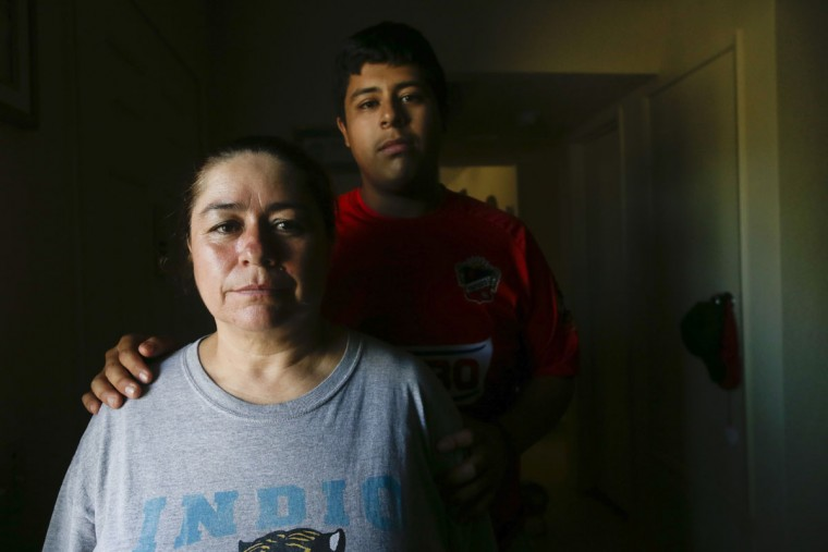 In this May 1, 2015 picture, Jose Alcantara, 17, behind, poses with his mother, Marta Sanchez, 45, in Mecca, Calif. Alcantara has become an activist for his mother, whose bronchitis worsened after the family moved to Mecca in 2010. The family believes dust from the exposed Salton Sea lakebed exacerbates respiratory illnesses in the region. (AP Photo/Gregory Bull)