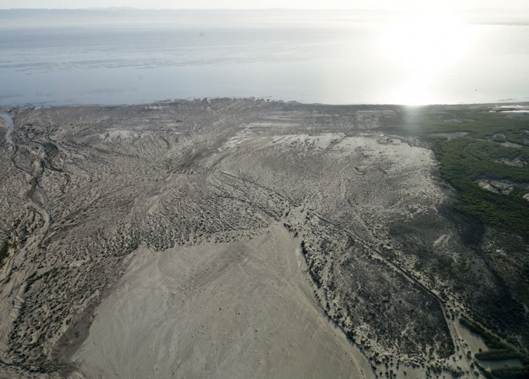 """In this May 1, 2015 aerial picture, exposed lakebed of the Salton Sea dries out near Niland, Calif. Often called the """"The Accidental Sea,"""" because it was created when the Colorado River breached a dike in 1905, Salton Sea now faces a looming calamity as coastal Southern California clamors for more water. (AP Photo/Gregory Bull)"""