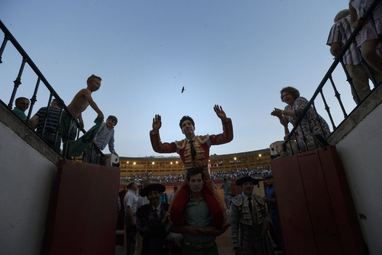 In this photo taken Saturday, May 30, 2015, Spanish bullfighter Alvaro Lorenzo leaves the bullring on the shoulders of supporters after and extraordinary performance on a bullfight in Aranjuez, near Madrid, Spain. Only after extraordinary performances bullfighters are allowed to be carried on the shoulders of supporters. Bullfighting is an ancient tradition in Spain. (AP Photo/Daniel Ochoa de Olza)
