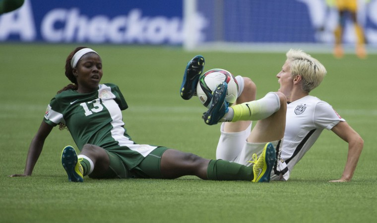 United States' Megan Rapinoe fights for control of the ball with Nigeria's Ngozi Okobi during the second half of a FIFA Women's World Cup soccer game Tuesday, June 16, 2105, in Vancouver, British Columbia, Canada. (Jonathan Hayward/The Canadian Press via AP)