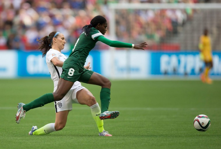Nigeria's Asisat Oshoala (8) leaps past United States' Lauren Holiday as she chases the ball during the first half of a FIFA Women's World Cup soccer game Tuesday, June 16, 2105, in Vancouver, British Columbia, Canada. (Darryl Dyck/The Canadian Press via AP)