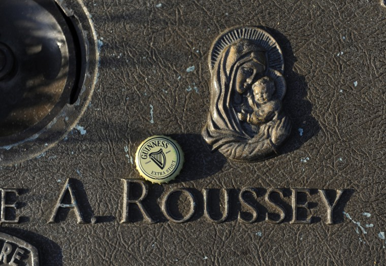 This is a detail from the grave of Officer Jamie A. Roussey, 22, of the Baltimore City police department. He was killed in an automobile accident on October 20, 2010 when his patrol vehicle collided with another car as he was responding to assist a fellow officer who was involved in a foot pursuit. He came from a law enforcement family, where his father, brother, uncle and cousin were Baltimore police officers. He served as an officer for one year and was survived by his parents and seven siblings. (Visitors to the gravesites often leave meaningful mementos such as this Guinness bottle cap. ) (Barbara Haddock Taylor/Baltimore Sun)