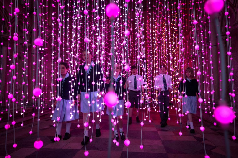 Children explore the new Squidsoup light installation, Enlightenment, in the North Porch of Salisbury Cathedral on June 12, 2015 in Salisbury, England. The installation, which is made up of around 6000 points of colour changing light bulbs suspended from the ceiling, is part of the Cathedral's celebrations for the 800th anniversary of the Magna Carta. (Photo by Matt Cardy/Getty Images)
