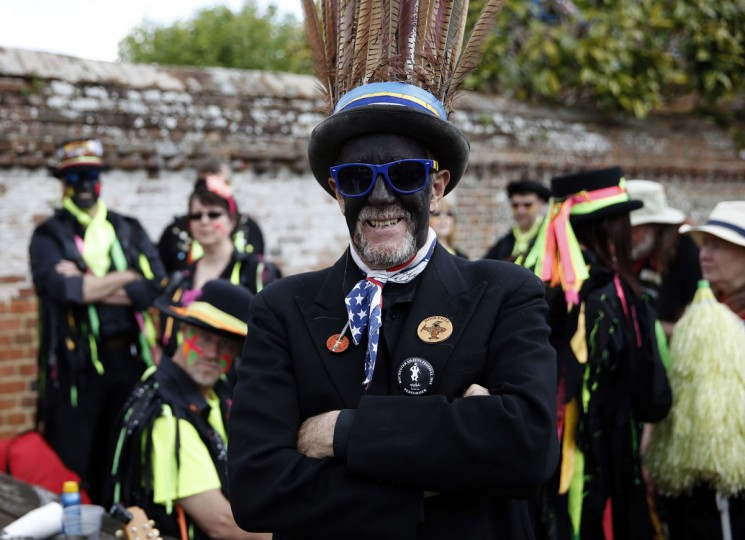 "A Hook Eagle Morris man (C) poses for a photograph as dancers gather in The Bury during the Clogg and Morris Festival, in Odiham, some fifty miles west of London on May 23, 2015, as part of the 800th anniversary celebrations of the signing of the Magna Carter. The Magna Carta, Latin for ""the Great Charter,"" was a charter agreed by King John of England on 15 June 1215, and was drafted by the then Archbishop of Canterbury, Stephen Langton, to make peace between the unpopular King and a group of rebel barons, and promising amongst other things, the protection of church rights. (AFP Photo/Adrian Dennis)"