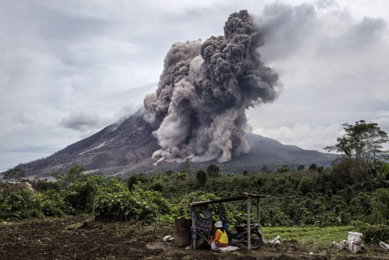 A local farmer sits on her fields as Mount Sinabung spews pyroclastic smoke, seen from Tiga Kicat village in Sukanalu village, North Sumatra, Indonesia. According The National Disaster Mitigation Agency, more than 10,000 villagers have fled their homes since the authorities raised the alert status of Mount Sinabung erupting to the highest level. (Ulet Ifansasti/Getty Images)