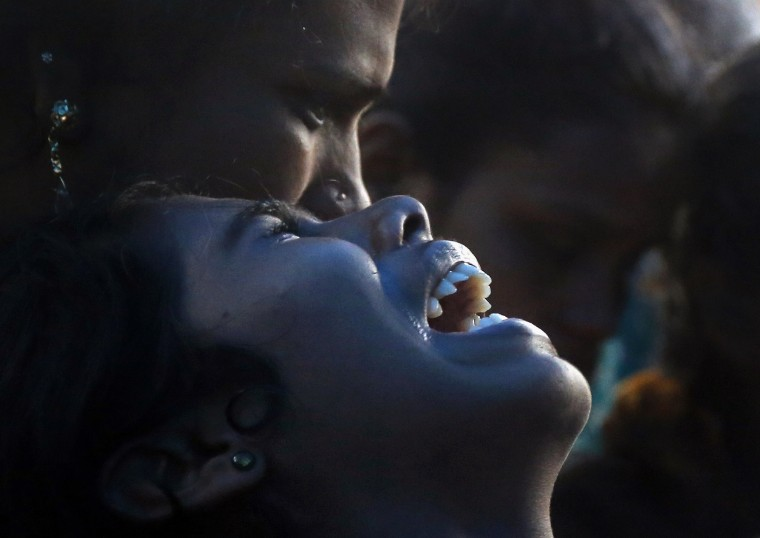 An Indian woman cries over the death of her family member who died after drinking tainted liquor at his funeral in Mumbai, India. The death toll from drinking tainted liquor in a Mumbai slum climbed to more than 80 in the worst incident of its kind in more than a decade, police said.(Rajanish Kakade/Associated Press)