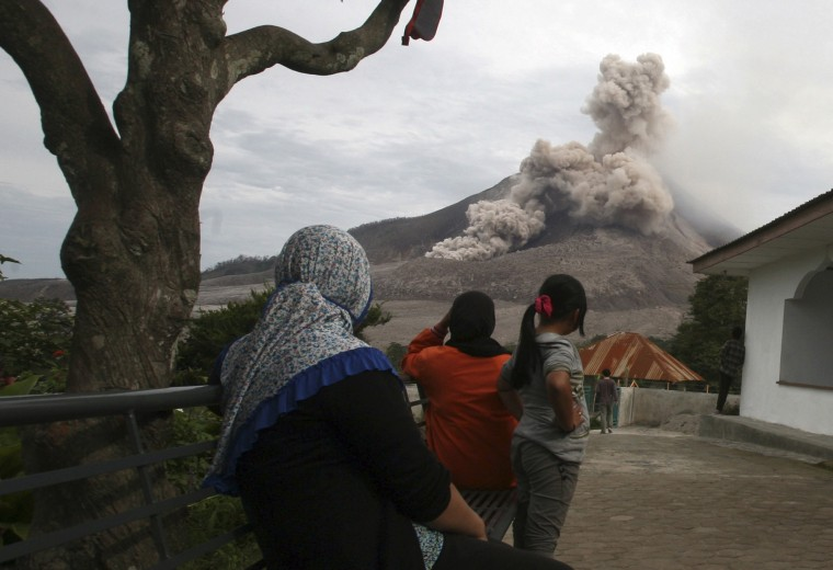 Indonesian women watch Mount Sinabung release pyroclastic flows in Tiga Serangkai, North Sumatra, Indonesia. Mount Sinabung, one of about 130 active volcanoes in the country, has been put at the highest alert level since June 2 due to the growing size of its lava dome. (Binsar Bakkara/Associated Press)