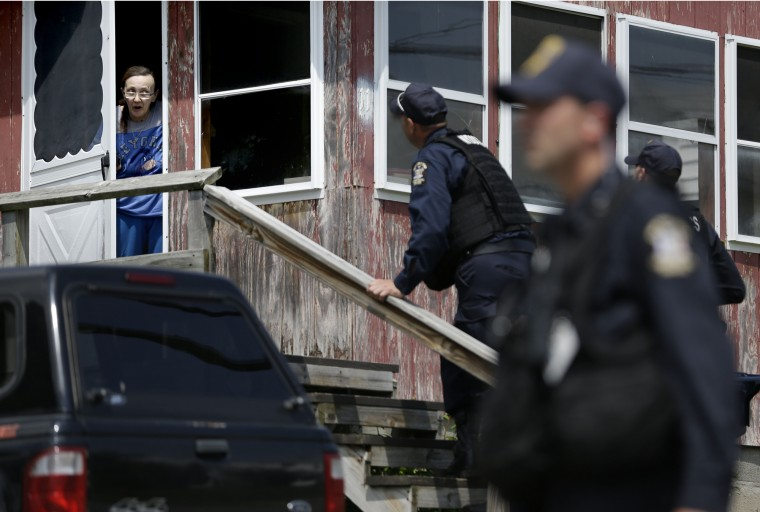 Law enforcement officers question a woman in Dannemora, N.Y., while searching houses near the maximum-security prison in northern New York where two killers escaped using power tools. State Police said the fifth day of searching will entail going from house to house in Dannemora, where David Sweat and Richard Matt cut their way out of the Clinton Correctional Facility. (Seth Wenig/Associated Press)