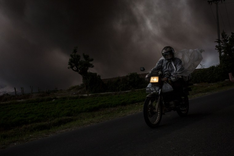 A man ride a motorcycle as Mount Sinabung spews pyroclastic smoke, seen from Tiga Kicat village in Karo District, North Sumatra, Indonesia. According to The National Disaster Mitigation Agency, more than 10,000 villagers have fled their homes since the authorities raised the alert status of Mount Sinabung erupting to the highest level. (Ulet Ifansasti/Getty Images)