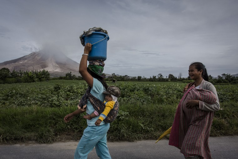 Women carry their children as walk to their fields as Mount Sinabung spews smoke, seen from Tiga Kicat village in Karo District, North Sumatra, Indonesia. According to The National Disaster Mitigation Agency, more than 10,000 villagers have fled their homes since the authorities raised the alert status of Mount Sinabung erupting to the highest level. (Ulet Ifansasti/Getty Images)