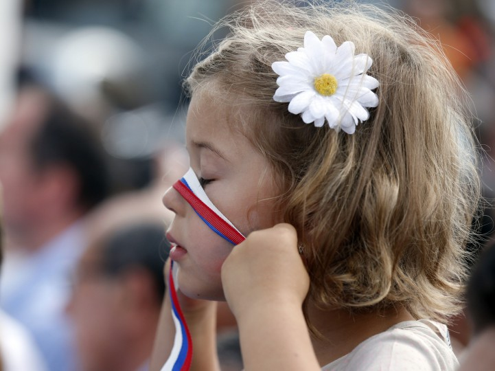 A girl plays with a ribbon in the colors of the Russian flag as she waits to see Russian President Vladimir Putin at the 2015 Expo, in Rho, near Milan, Italy. Putin was meeting Wednesday with Italian officials and Pope Francis as the U.S. sought to encourage the Vatican to join the West in condemning Moscow's actions in Ukraine. (Luca Bruno/Associated Press)