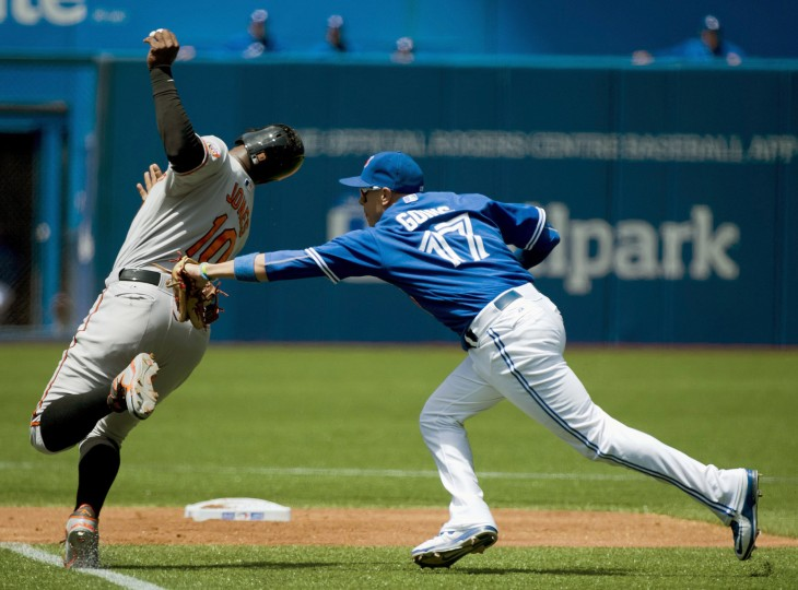 Toronto Blue Jays second baseman Ryan Goins (17) tags out Baltimore Orioles DH Adam Jones (10) at second base during the first inning of a baseball game in Toronto on. (Nathan Denette/The Canadian Press via AP)