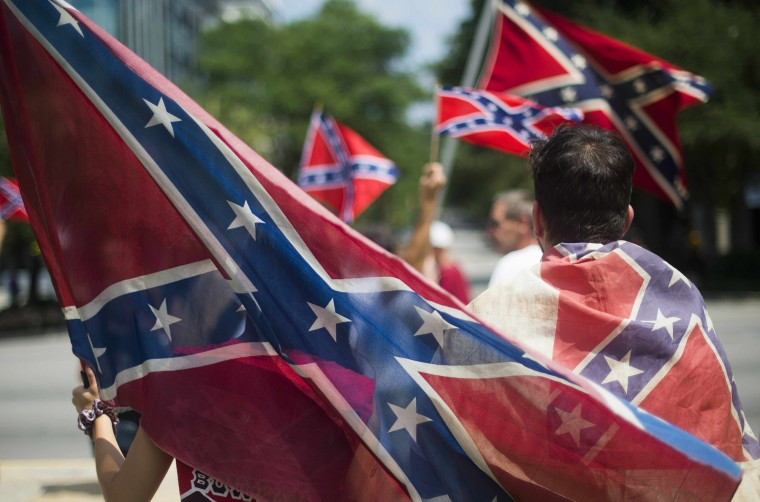 "Pro-confederate flag demonstrators march to the South Carolina State House in Columbia, South Carolina. There has been a growing clamor for the flag -- branded ""a reminder of systemic oppression and racist subjugation"" by President Barack Obama on Friday -- to be removed from the grounds of the state house in Columbia. Once flown by the rebel army of the slave-owning South, the confederate flag is seen by some as a symbol of regional heritage, but by many more as an ugly reminder of racism's cruel legacy. (Jim Watson/AFP-Getty Images)"