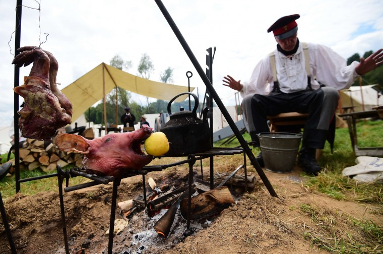 "A re-enactor sits next to a pig head cooked over a fire at the Allied camp ahead of the second and last part of a reenactment of the Battle of Waterloo, ""The Allied counterattack"", during the celebrations of the 200th anniversary of The Battle of Waterloo in Waterloo. Ceremonies to mark the 200th anniversary of the Battle of Waterloo were scheduled for June 17 to 20. Nearly 200,000 spectators were expected to flock to the site for a giant sound-and-light show on June 18, followed by two days of battle reenactments described as the largest of their kind in the world. (Emmanuel Dunand/AFP-Getty Images)"