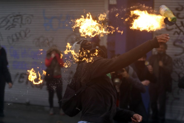 A protester throws a petrol bomb towards the police during a march, demanding more participation in the education reform discussions, in Santiago, Chile. Teachers began on June 1 an indefinite strike in protest against the newest education reforms that are being discussed in Congress and promoted by Chile's President Michelle Bachelet's government. (Luis Hidalgo/Associated Press)