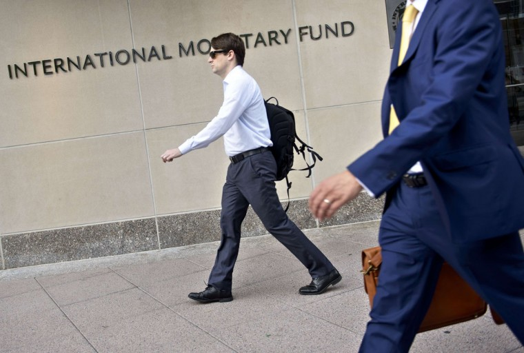 People walk past the headquarters of the International Monetary Fund June 30, 2015 in Washington, DC. Greece confirmed it would fail to make a key IMF repayment due on Tuesday, fanning fears of a chaotic eurozone exit on the same day the country's international bailout expires. (BRENDAN SMIALOWSKI/AFP/Getty Images)