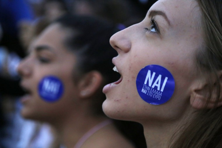 A demonstrator shouts slogans as the sticker on her cheek reading ''YES to Greece, Yes to Euro'' during a rally organized by supporters of the YES vote for the upcoming referendum in front of the Greek Parliament in Athens, Tuesday, June 30, 2015. (AP Photo/Petros Karadjias)