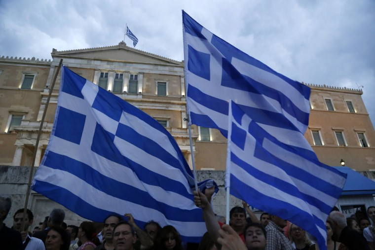 Demonstrators hold Greek flags during a rally organized by supporters of the YES vote to the upcoming referendum in front of the Greek Parliament in Athens, Tuesday, June 30, 2015. (AP Photo/Petros Karadjias)